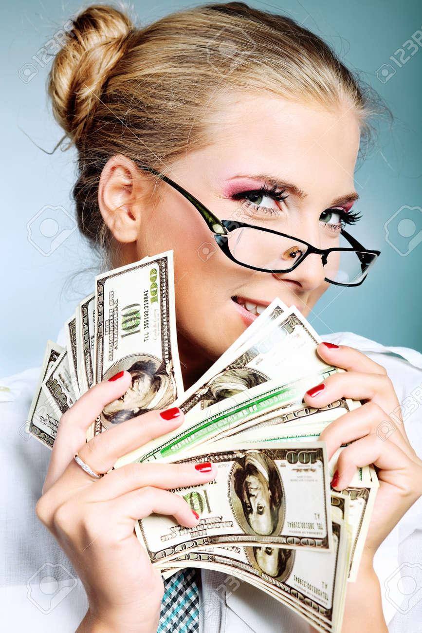 Beautiful businesswoman holding money. Studio shot over grey background. Stock Photo - 9140586