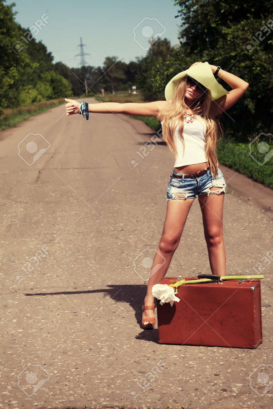 Pretty young woman hitchhiking along a road. Stock Photo - 9962112