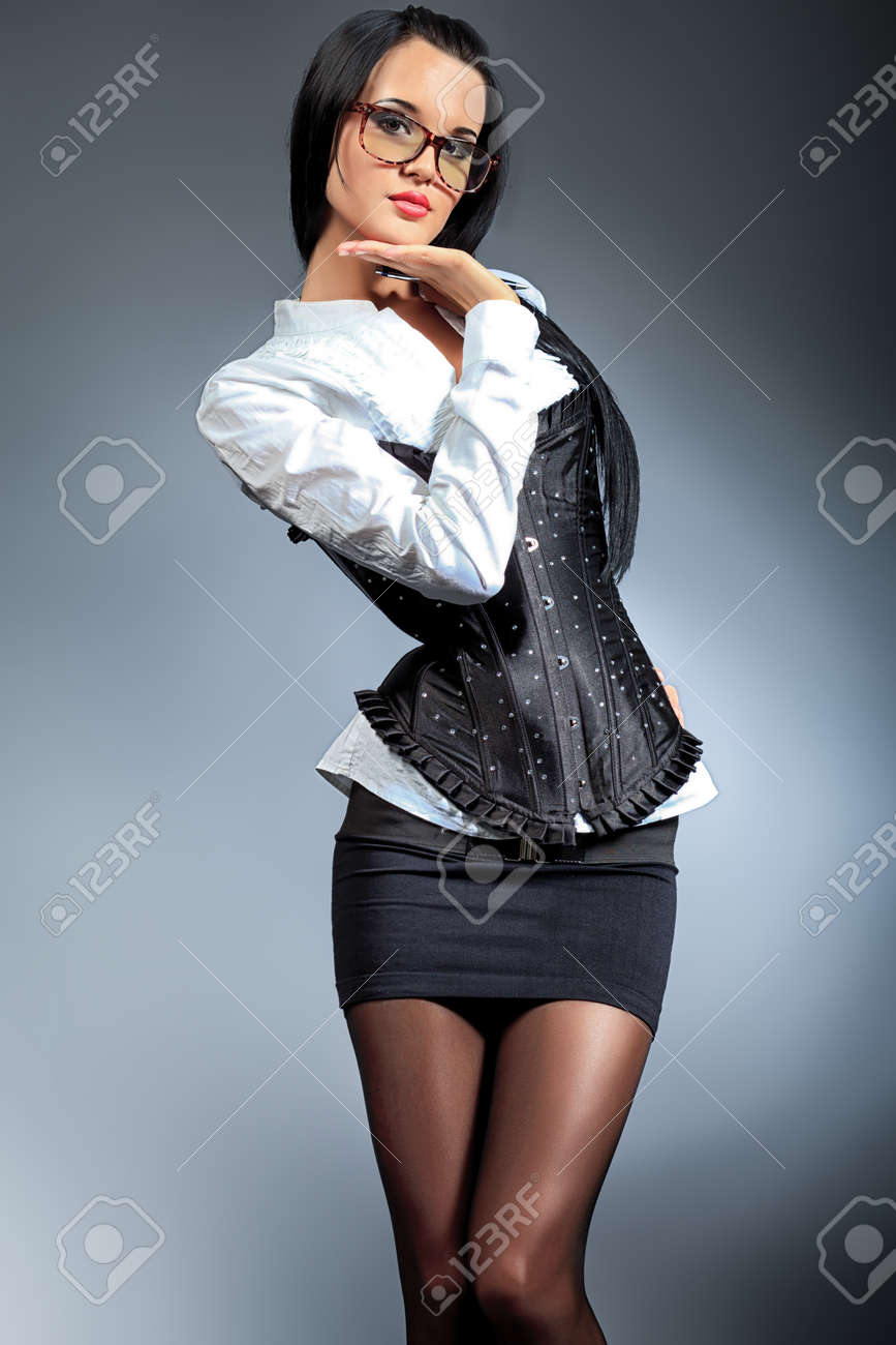 An attractive young woman in spectacles posing over grey background. Stock Photo - 10834953