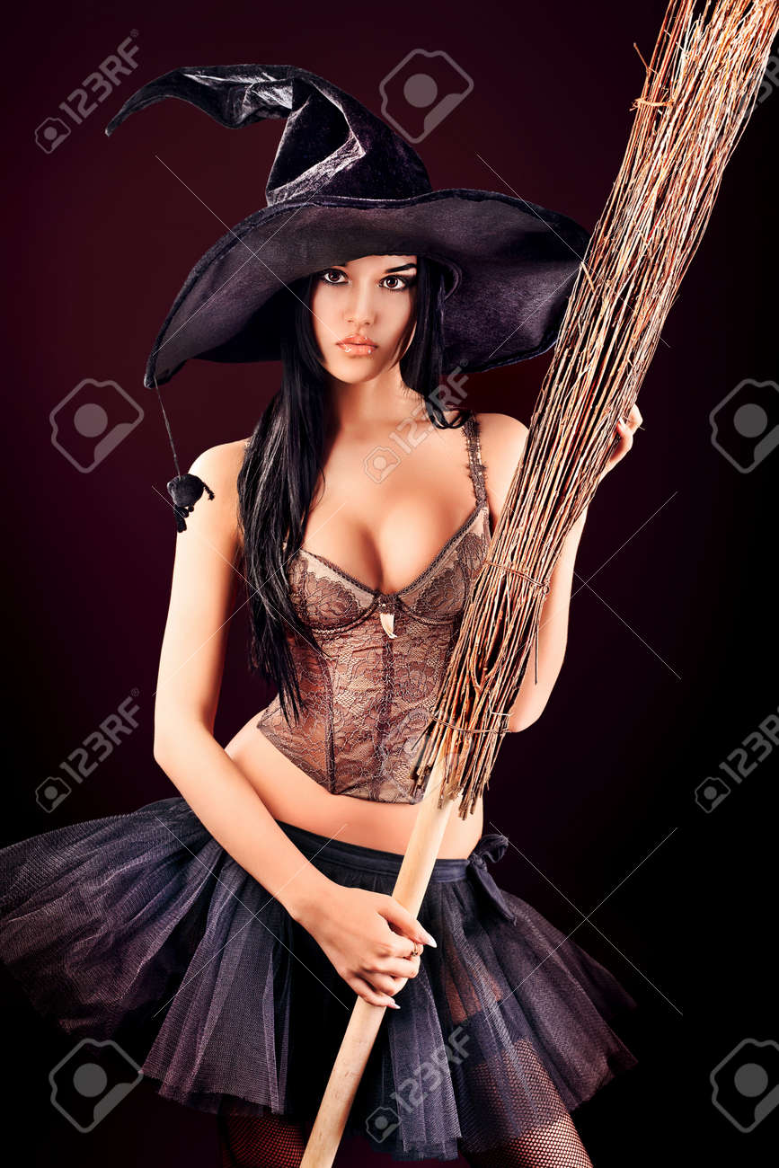 Charming halloween witch with broom over black background. - 13339620