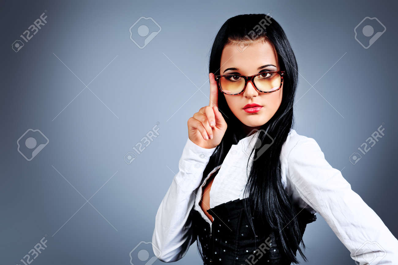 An attractive young woman in spectacles posing over grey background. Stock Photo - 11185218