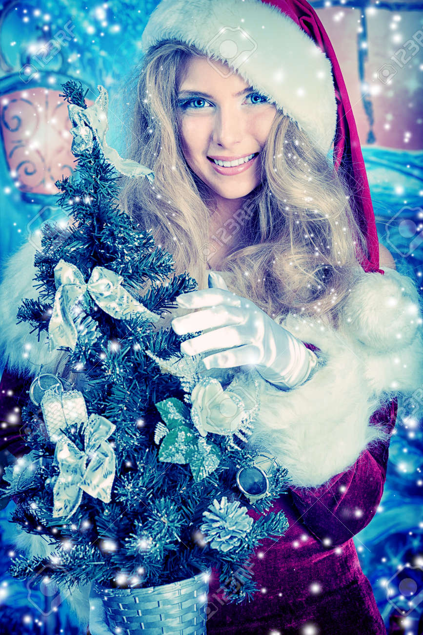 Beautiful young woman in Santa Claus clothes over Christmas background. Stock Photo - 11261516