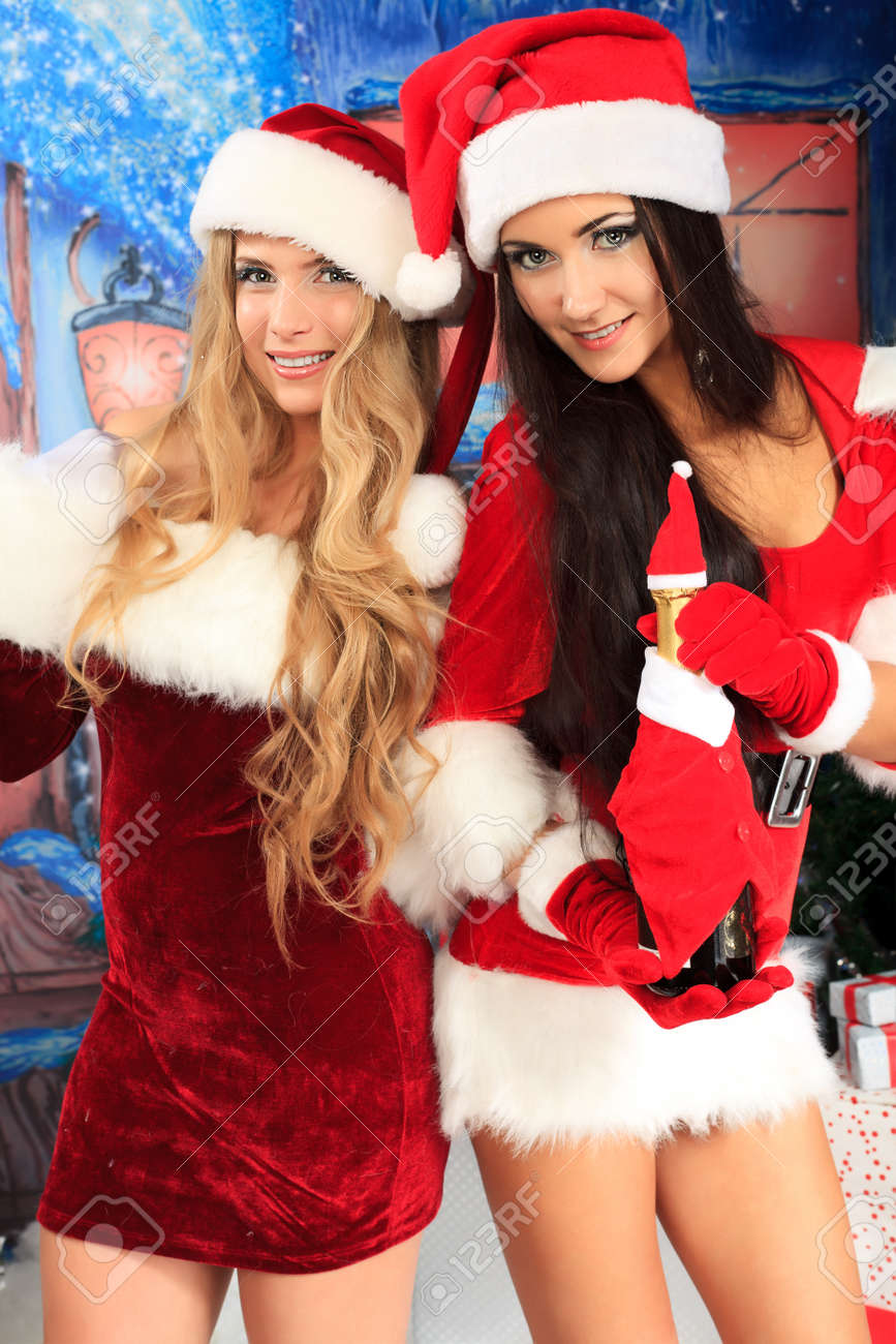Two beautiful young women in Christmas clothes posing over Christmas background. Stock Photo - 11340700
