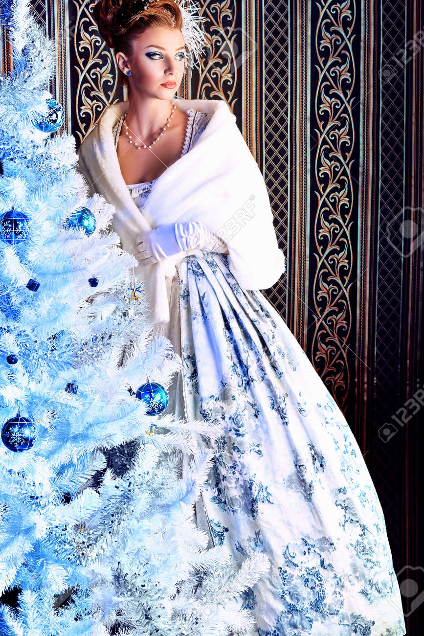 Portrait of the elegant woman posing with Christmas tree over vintage background. Stock Photo - 11340797