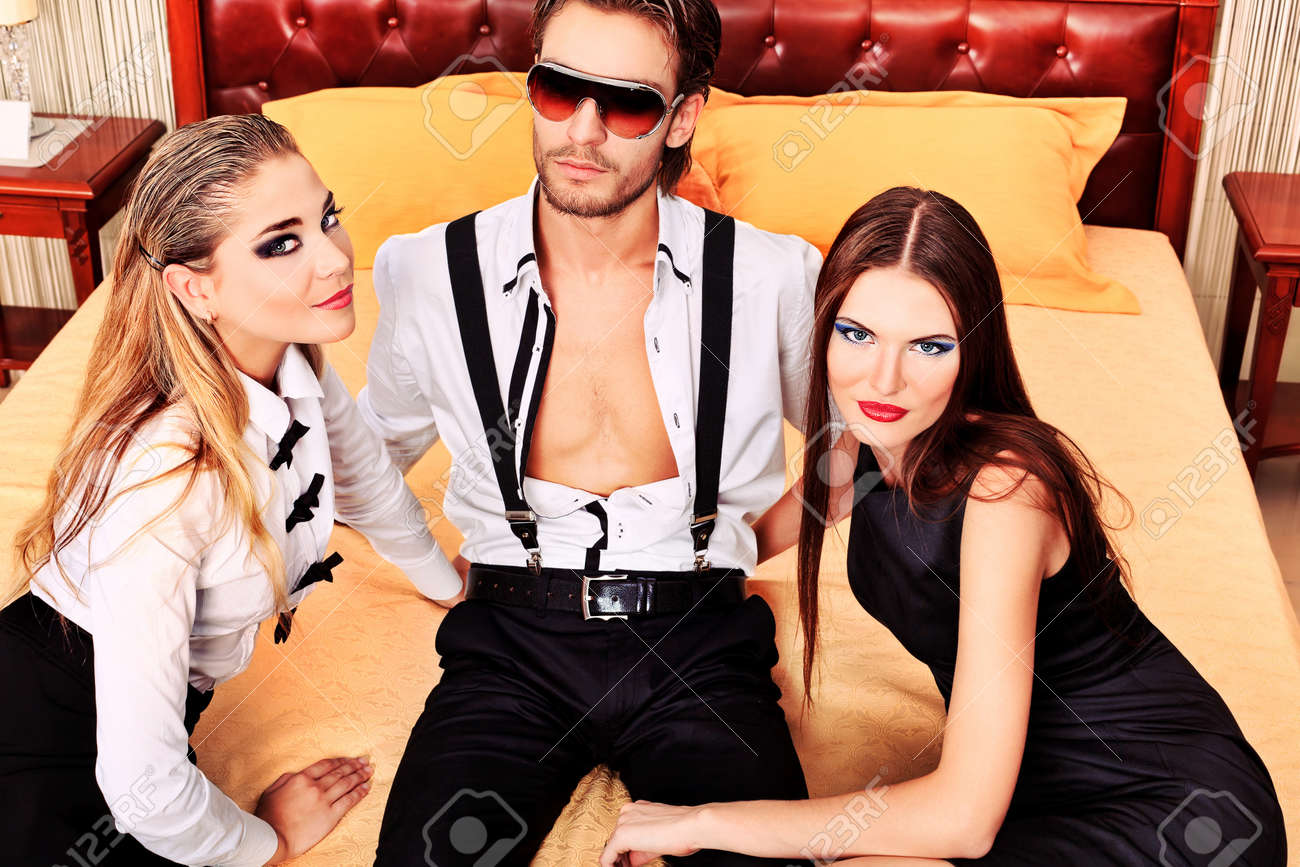 Portrait of a handsome fashionable man with two charming women posing in the interior. Stock Photo - 11692242