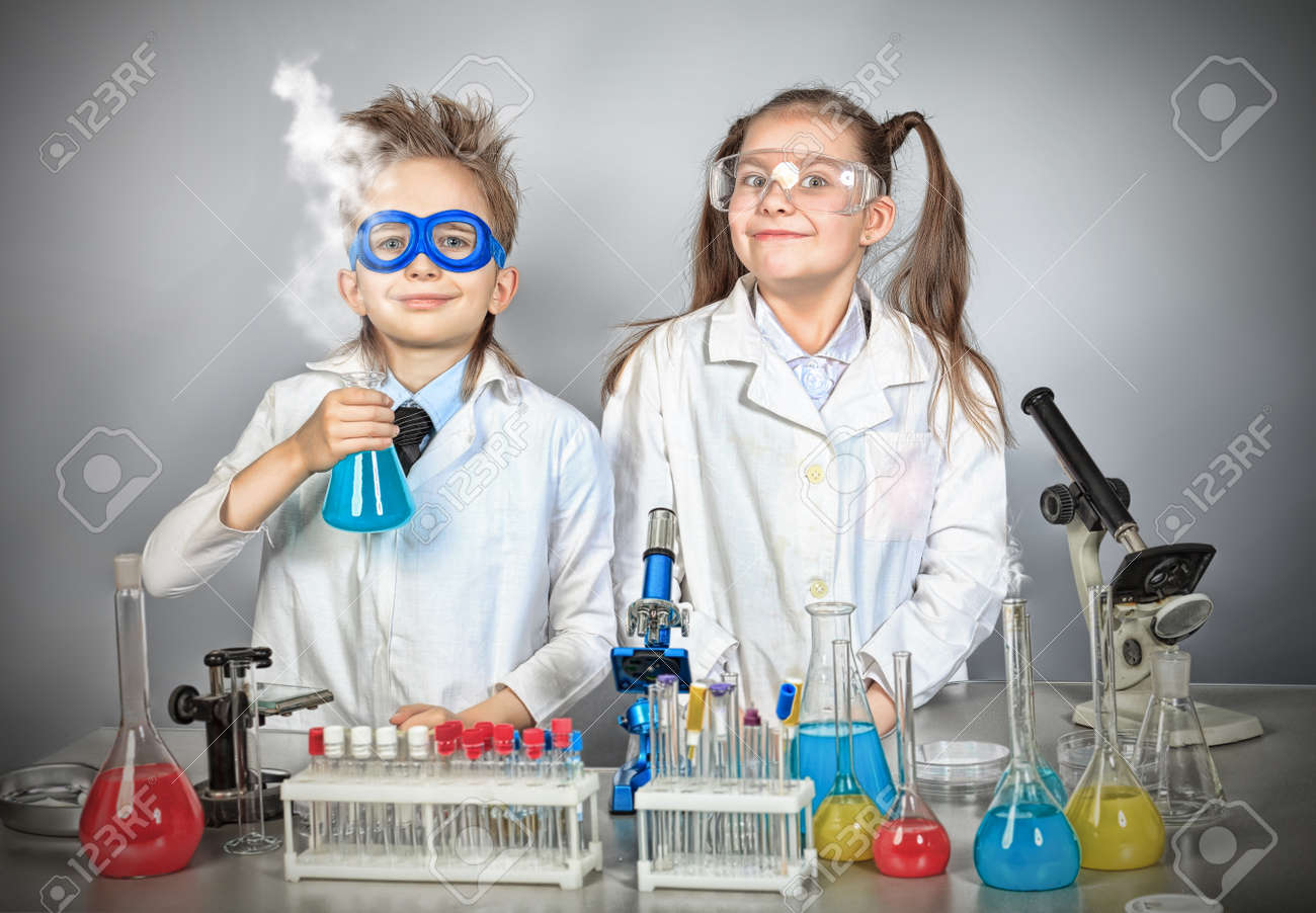 Two children making science experiments. Education. - 12521777