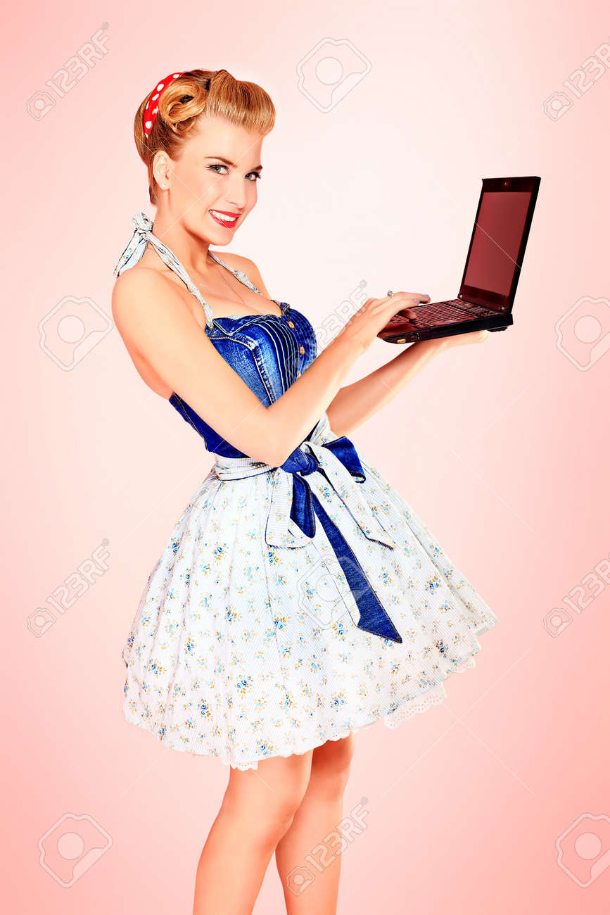 Smart pin-up girl posing over pink background with a laptop. Stock Photo - 13637412