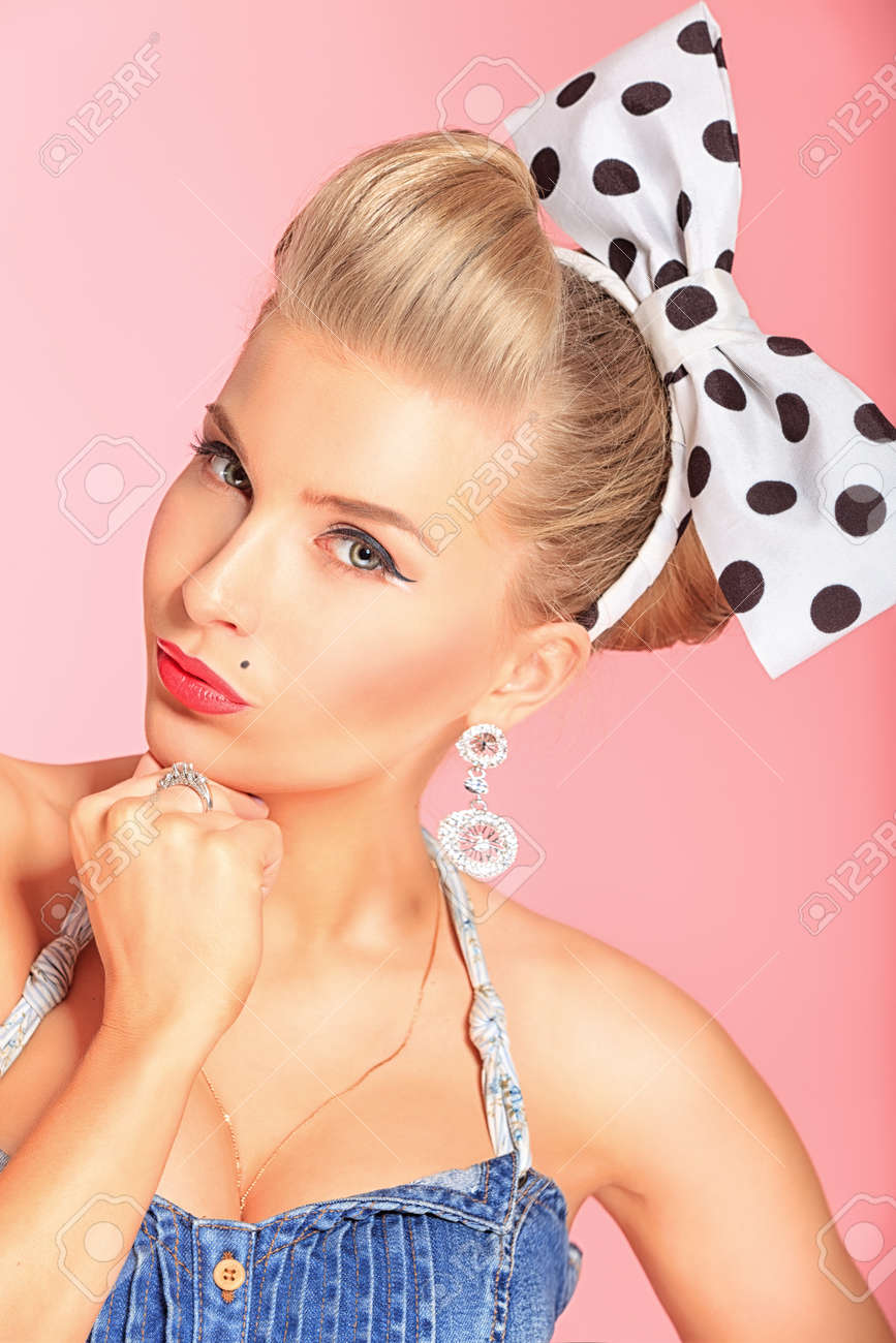 Beautiful young woman with pin-up make-up and hairstyle posing over pink background. Stock Photo - 13666647