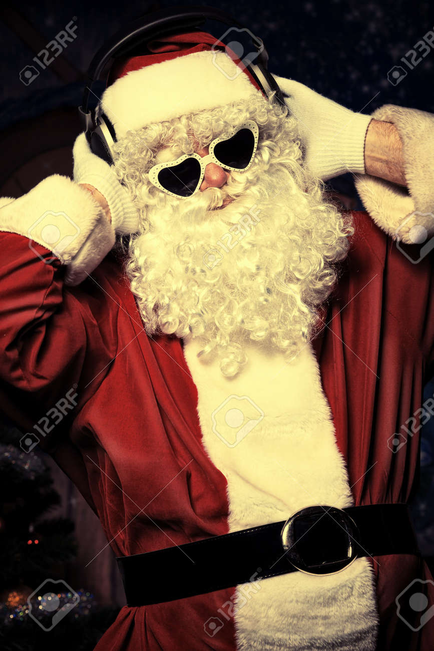 Santa Claus is listening to music in headphones. Christmas. Stock Photo - 15421780