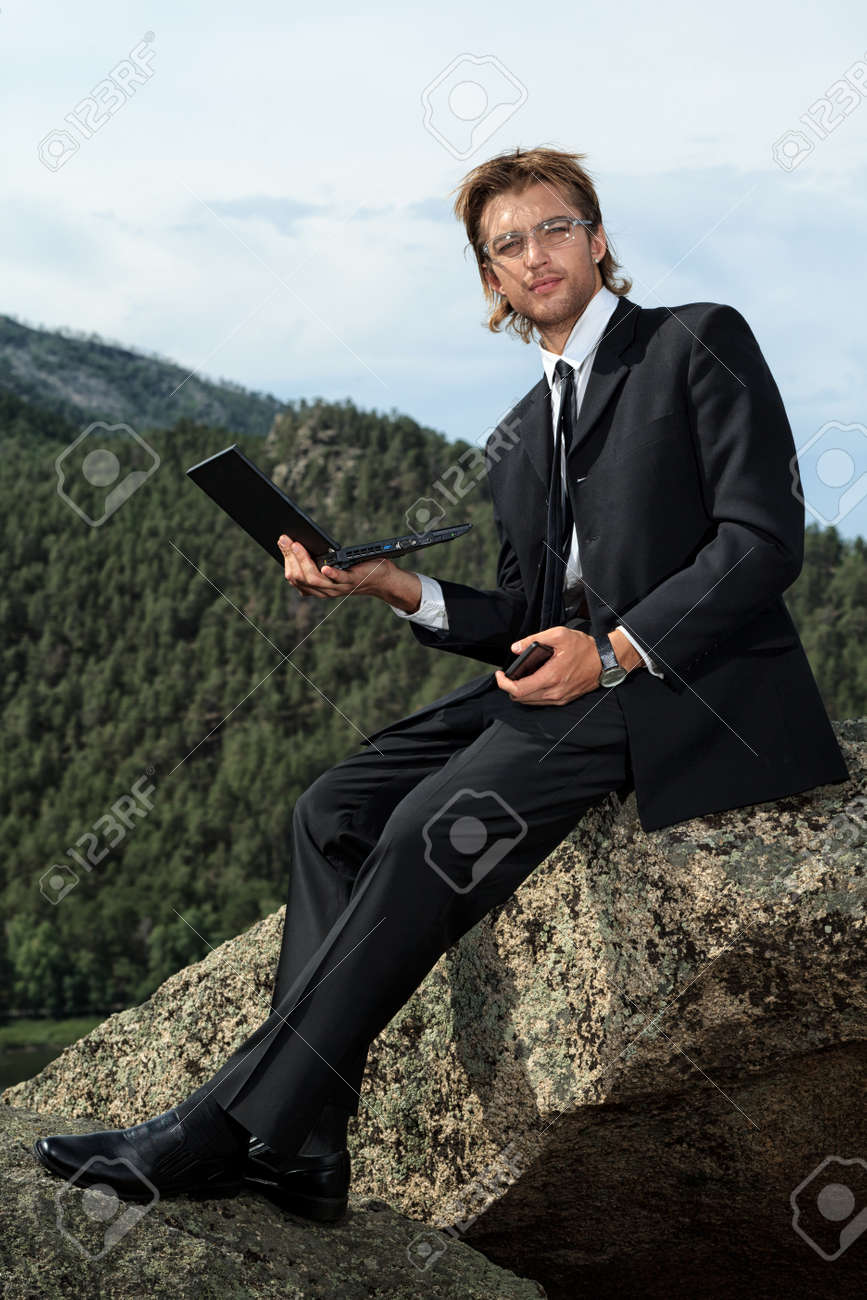 Successful business man working on a laptop on a peak of the mountain Stock Photo - 15400617