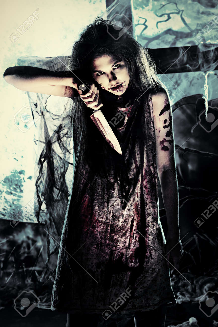 Bloodthirsty zombie with a knife standing at the night cemetery in the mist and moonlight. Stock Photo - 15539018