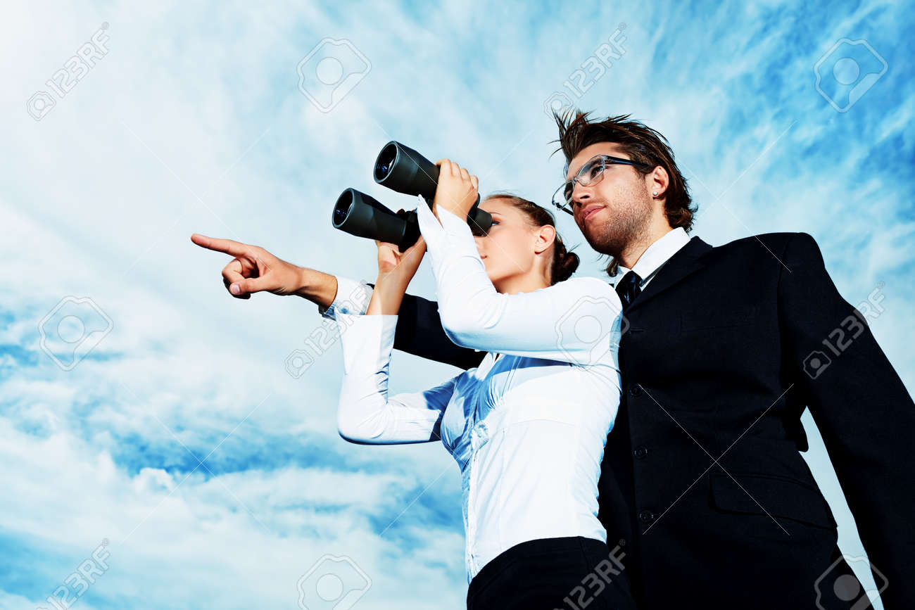 Successful business people standing over blue sky and purposefully looking away. - 15584698