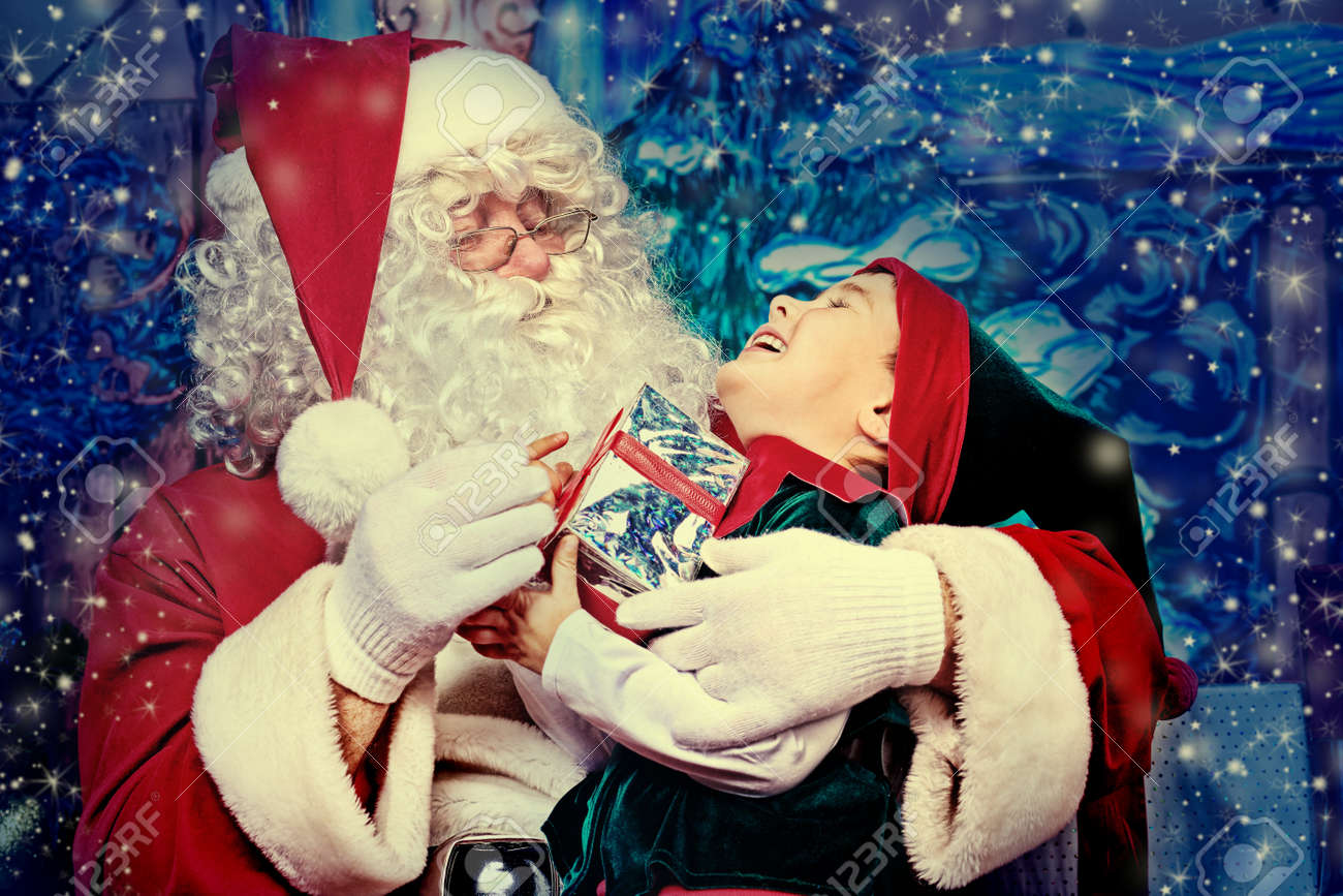 Santa Claus sitting with a little cute boy elf over Christmas background. Stock Photo - 15771281