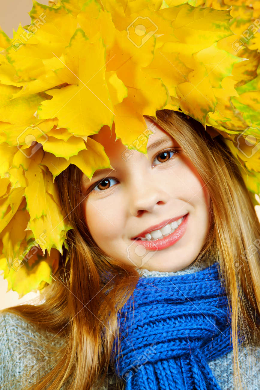 Portrait of a smiling girl in autumn clothes and a hat of maple leaves. Stock Photo - 15886969