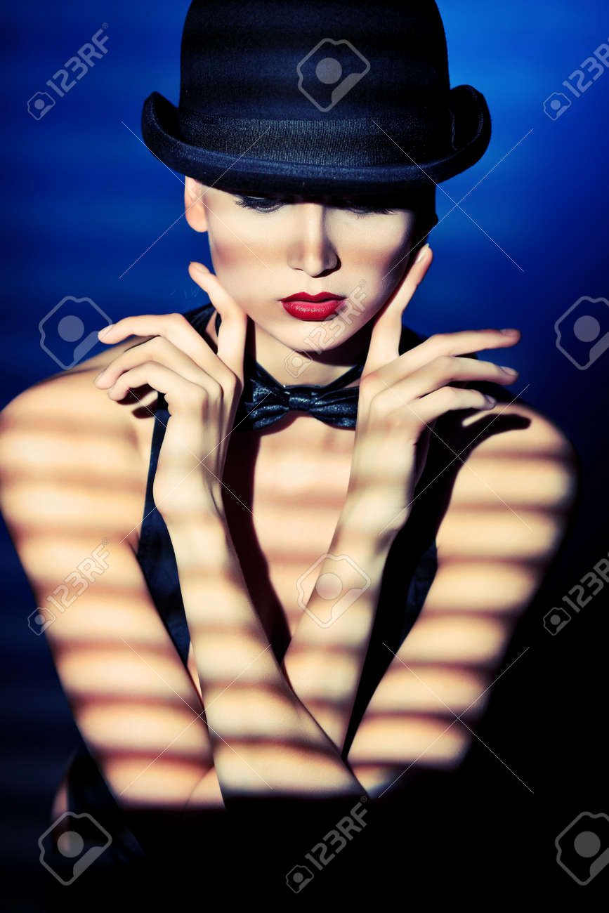 9b22daf5de2 Elegant young woman posing in vest and black pot hat. Light and shadow.  Stock