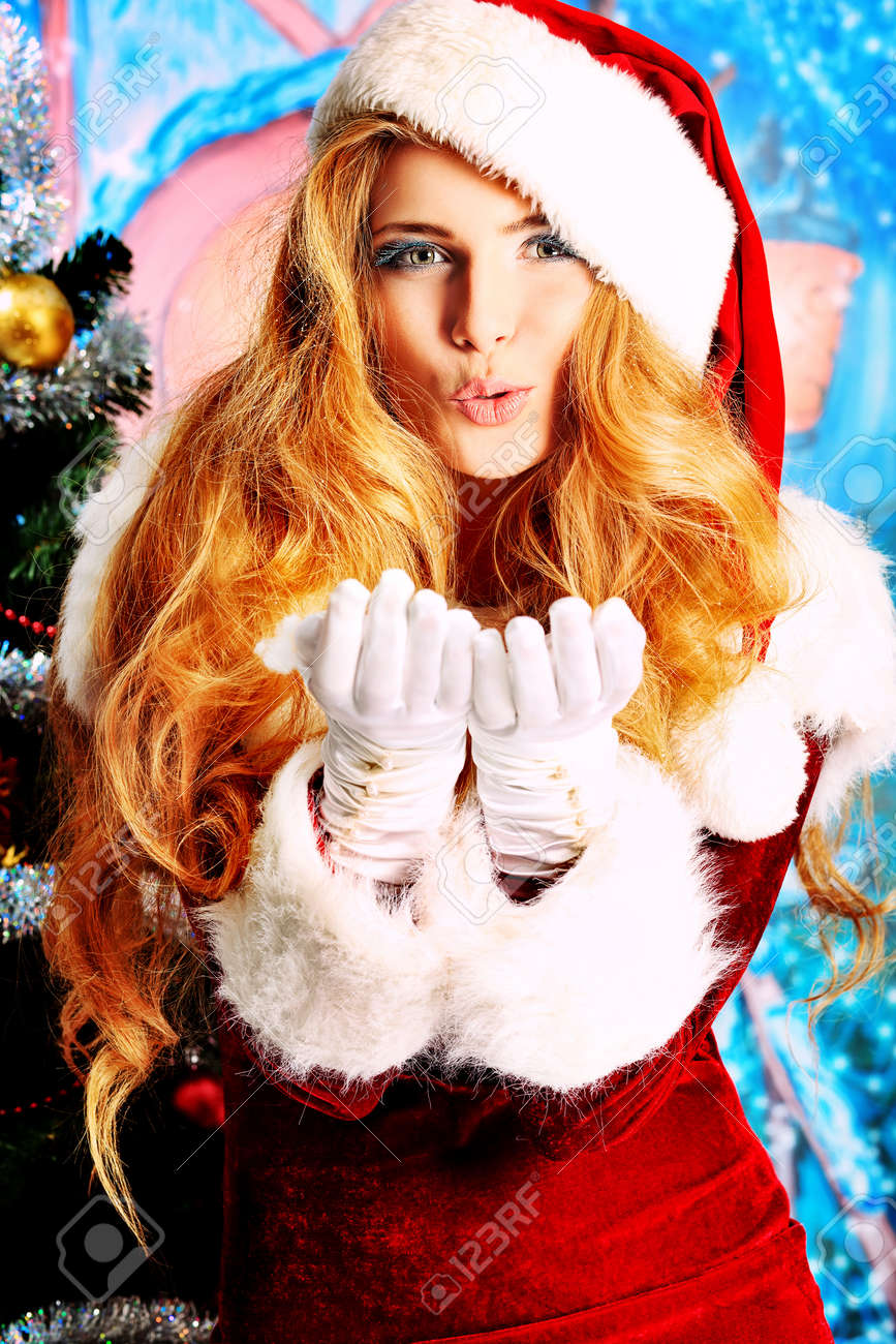 Beautiful young woman in Santa Claus clothes over Christmas background. Stock Photo - 16050640