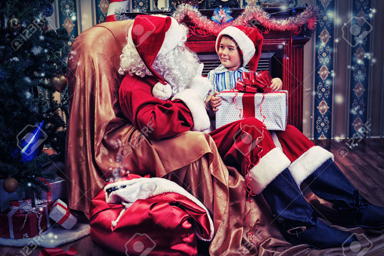 Santa Claus giving a present to a little cute boy near the fireplace and Christmas tree at home. Stock Photo - 16105631