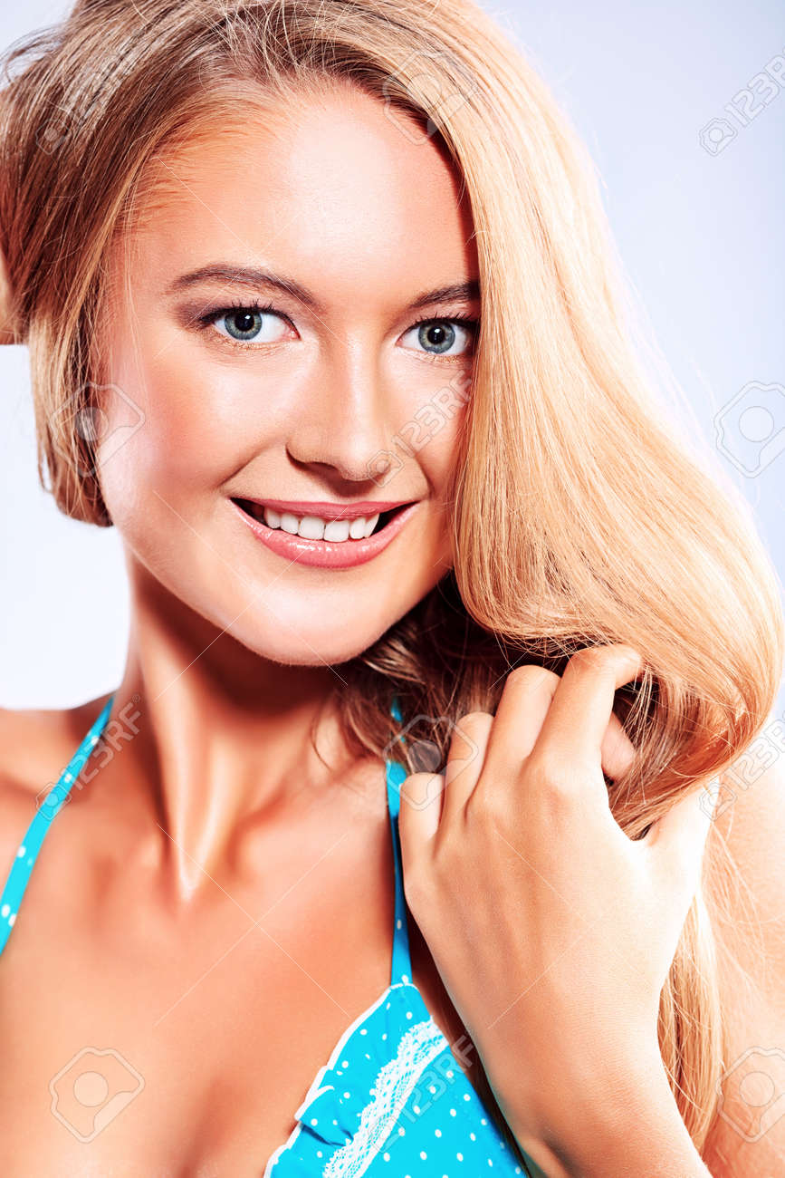 Smiling young woman posing in bikini over gray background. Stock Photo - 16305669