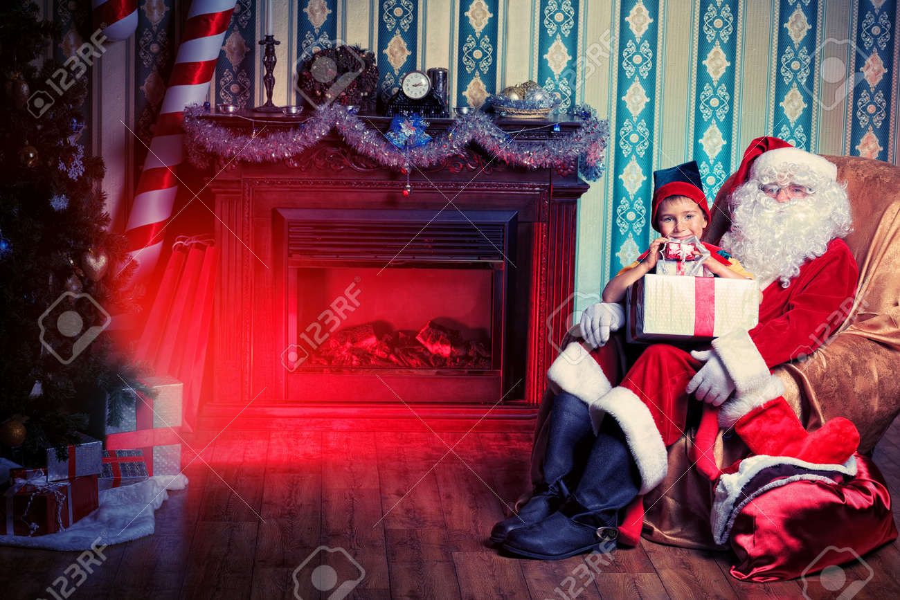 Santa Claus giving a present to a little cute boy at home. Stock Photo - 16354502