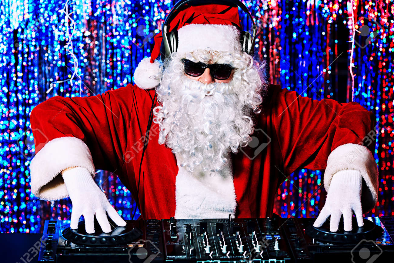DJ Santa Claus mixing up some Christmas cheer. Disco lights in the background. Stock Photo - 16551741