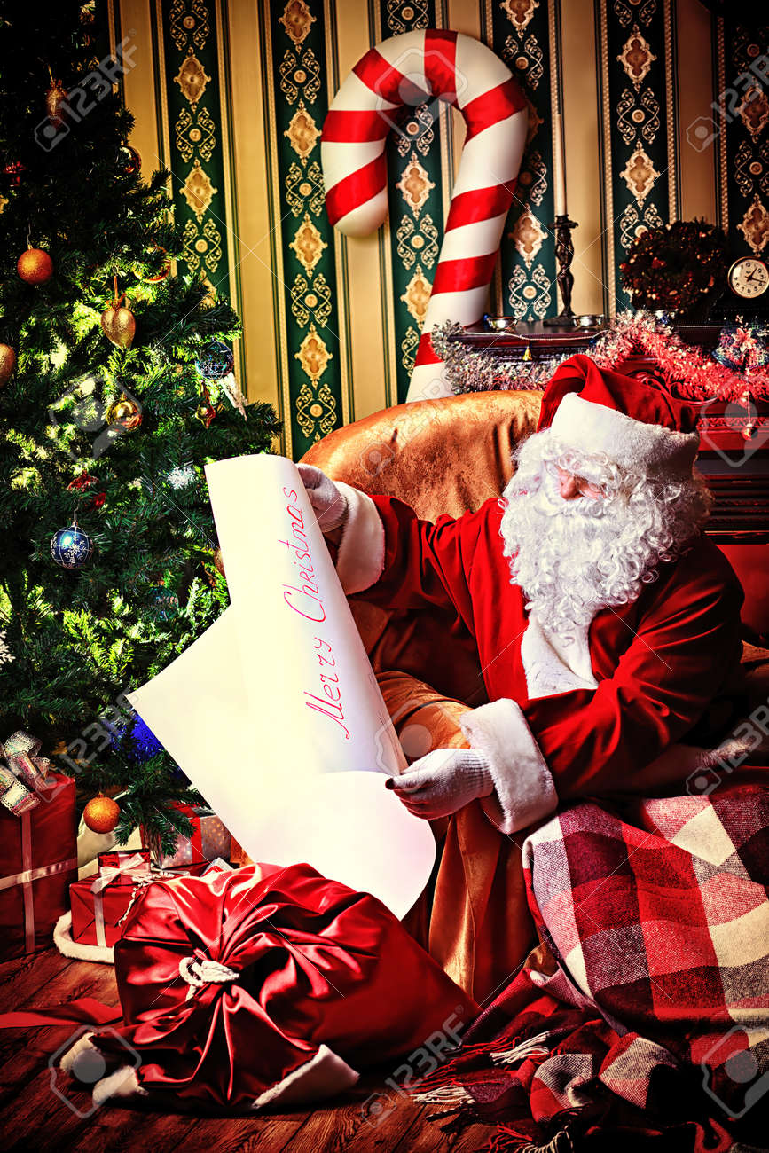 santa claus with a list of christmas presents sitting in a