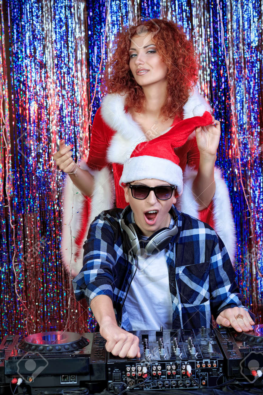DJ man mixing up some Christmas cheer with attractive Snow Maiden. Disco lights in the background. Stock Photo - 16619270