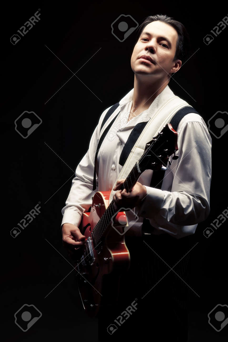 Portrait of a professional artist playing on guitar. Over black background. Stock Photo - 16641287