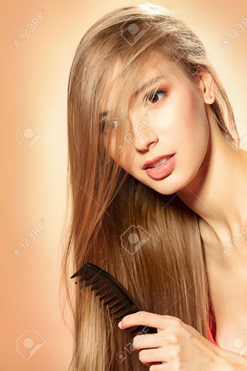Young pretty blonde woman combing her beautiful long hair. Stock Photo - 16671852