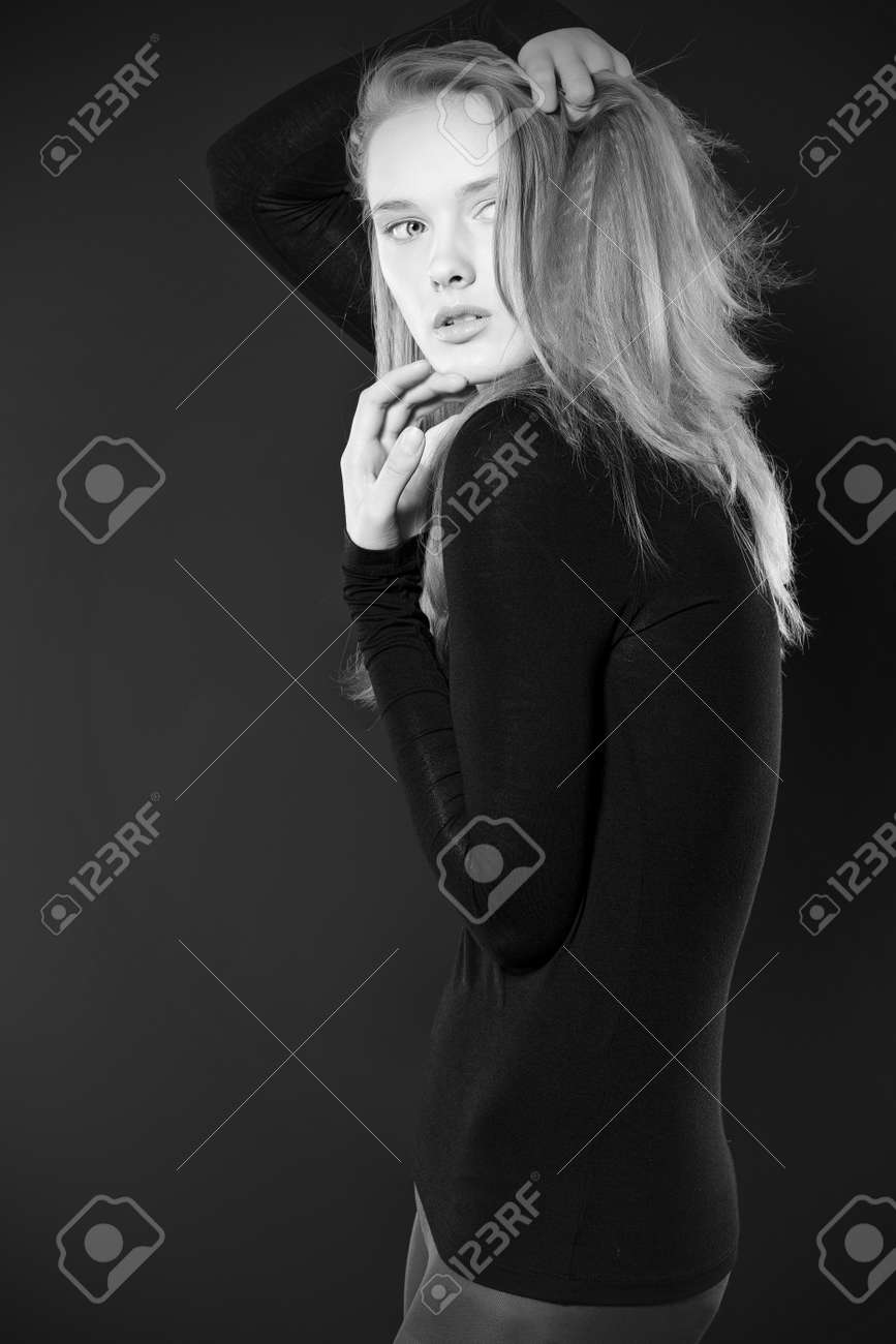 Portrait of a beautiful young woman in black blouse over dark background. Stock Photo - 16711704