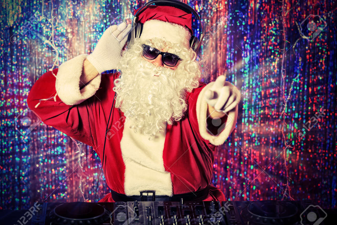 DJ Santa Claus mixing up some Christmas cheer. Disco lights in the background. Stock Photo - 16740097