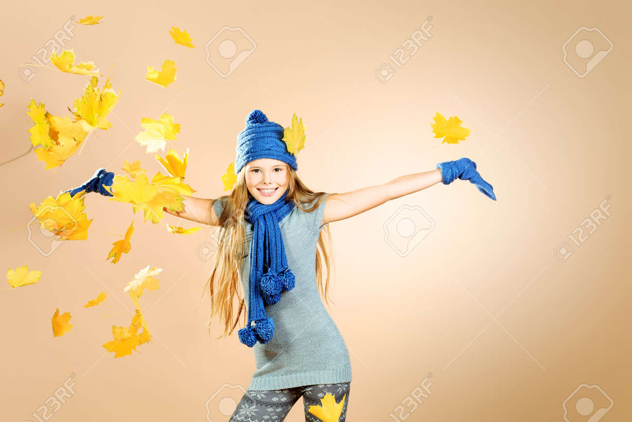 Joyful cute girl in autumn clothes throwing maple leaves Stock Photo - 17255331