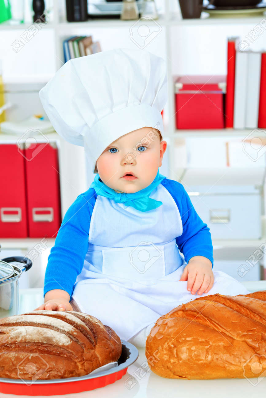 b030dc1f0 Cute small baby in the cook costume at the kitchen. Stock Photo - 17496058