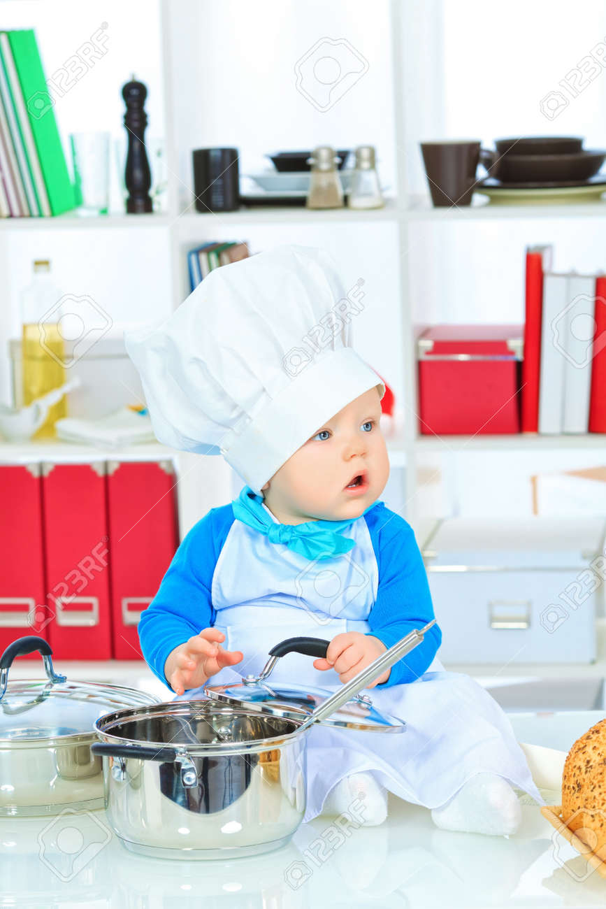 ec2d1f2c1 Cute small baby in the cook costume at the kitchen. Stock Photo - 17496048