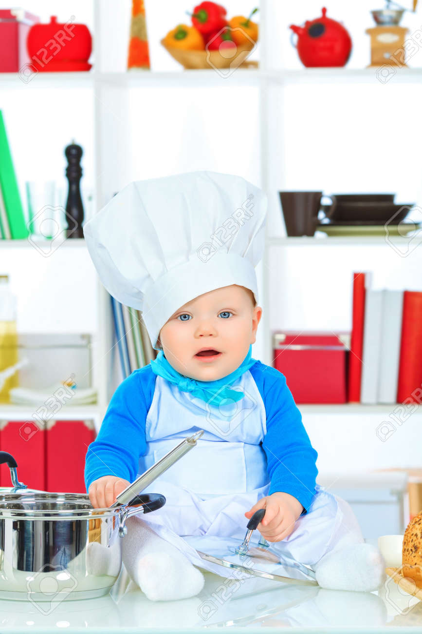 bfba14e68 Cute small baby in the cook costume at the kitchen. Stock Photo - 17496057