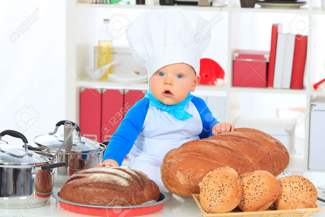 Cute small baby in the cook costume at the kitchen stock photo 17541855