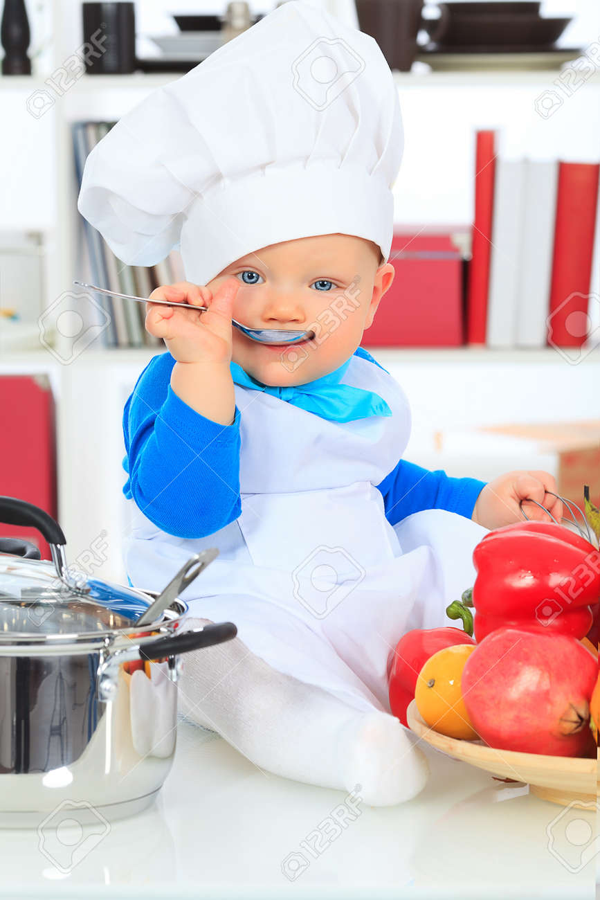 fd6a8de33 Cute small baby in the cook costume at the kitchen. Stock Photo - 17541836