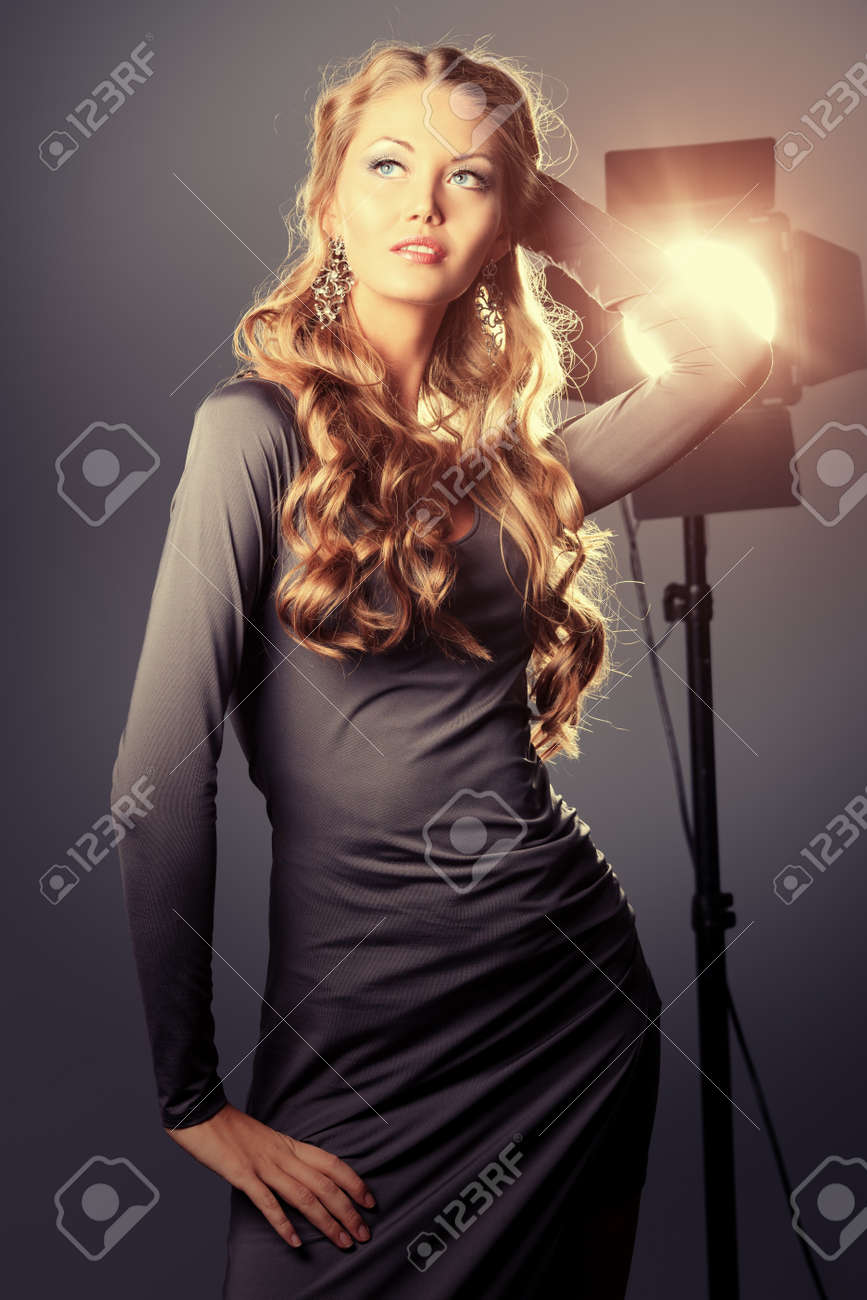 Beautiful female model posing at studio in the light flashes. Stock Photo - 18520253