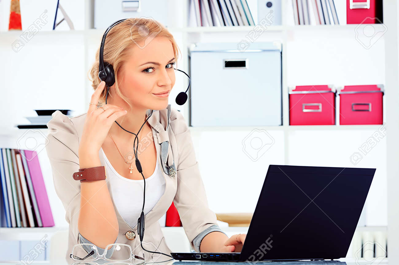 Portrait of smiling young woman operator in headset at office. Stock Photo - 19496276