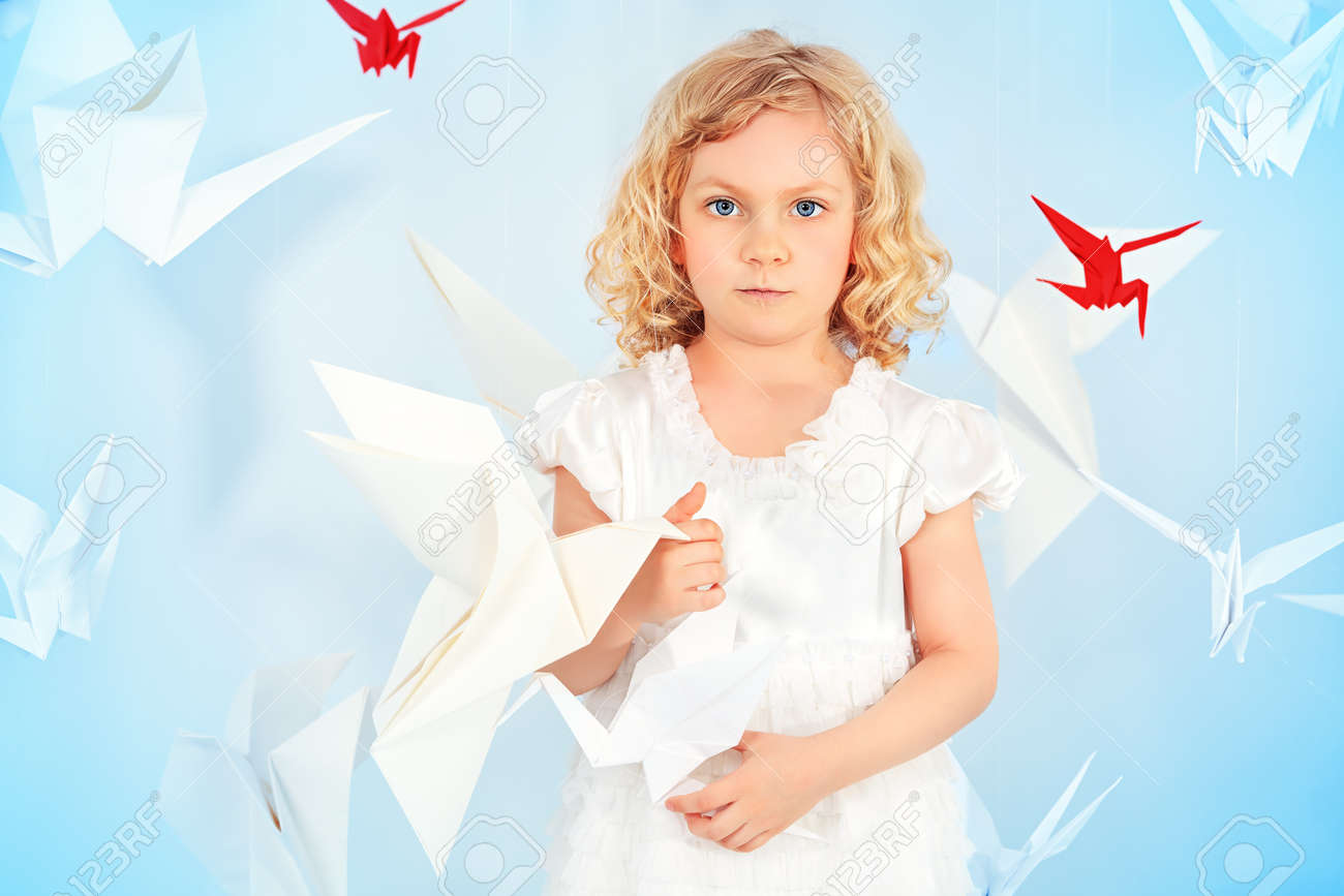 Beautiful little girl in her dream world surrounded with paper birds. Stock Photo - 19563694