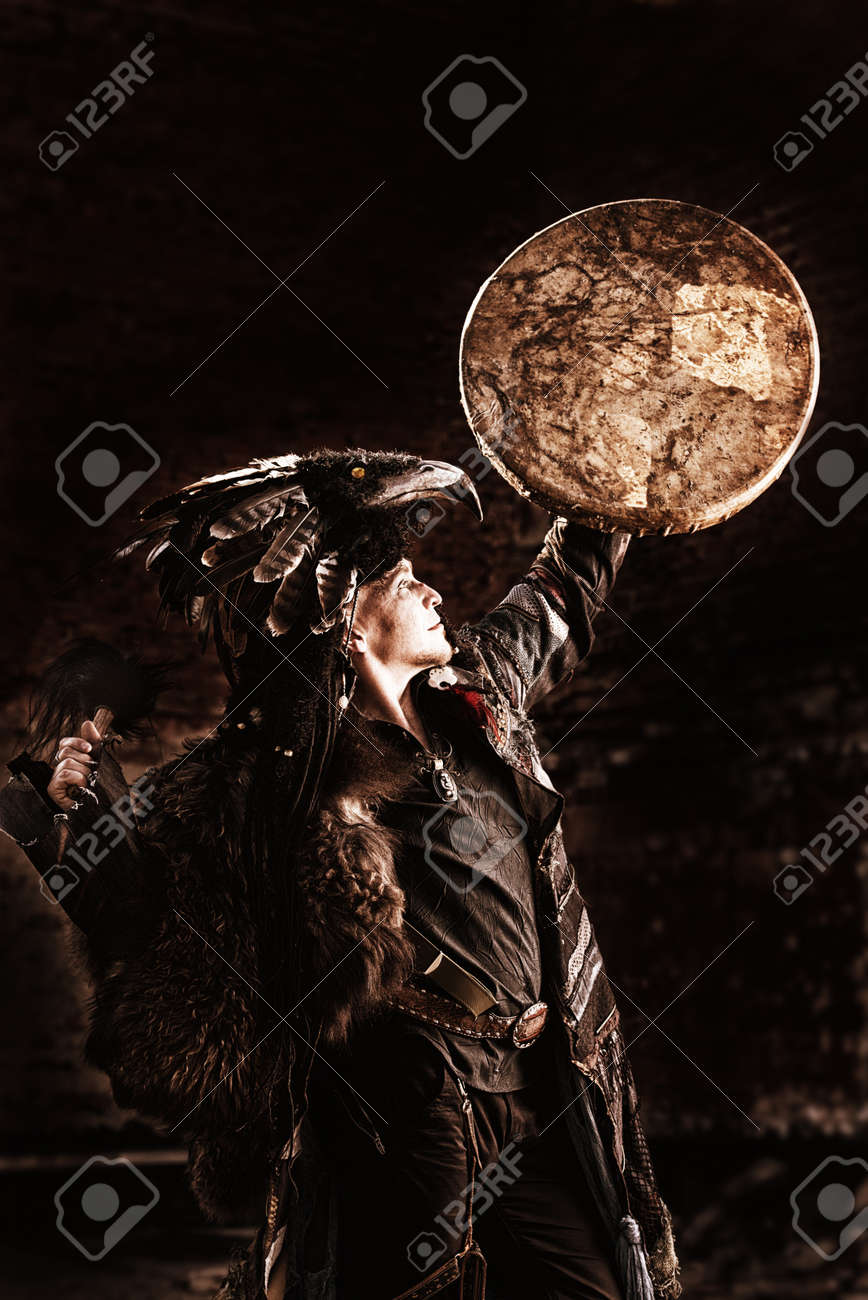 Portrait of a shaman dancing with a drum outdoor. - 22450065