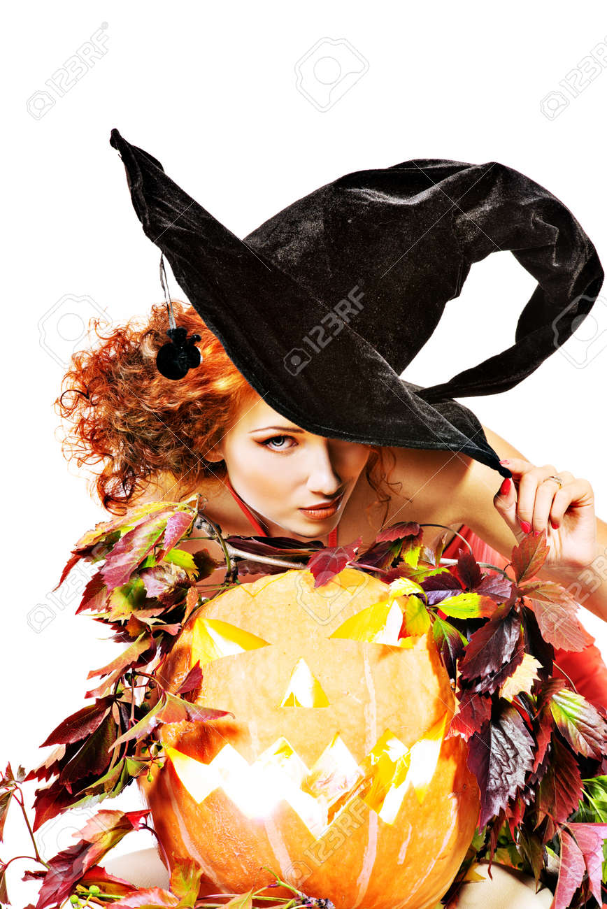 Beautiful red-haired witch casts a spell over pumpkins  Halloween  Isolated over white Stock Photo - 23331293