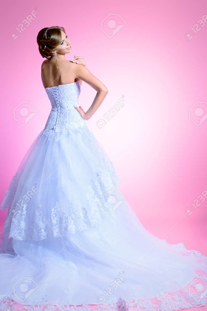 Beautiful charming bride in a luxurious dress standing with her back. Stock Photo - 23441226