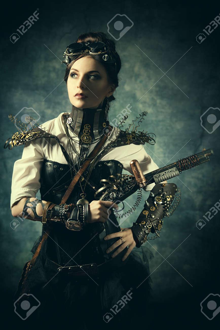 Portrait of a beautiful steampunk woman holding a gun over grunge wall. Stock Photo - 23456147