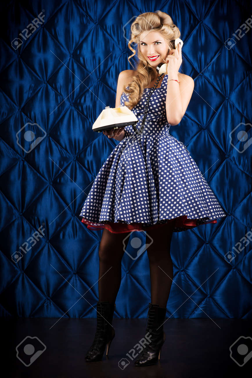 Charming pin-up woman with retro hairstyle and make-up talking on the phone. Stock Photo - 23831999