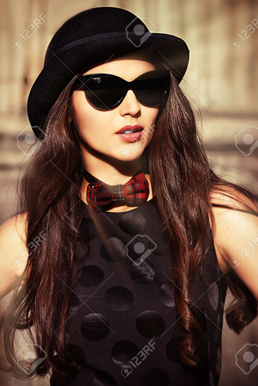 Beautiful brunette in bowler hat and bow-tie standing on the street of the old town. Retro style. Stock Photo - 24254003