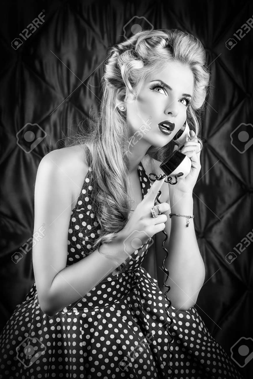 Charming pin-up woman with retro hairstyle and make-up talking on the phone. Stock Photo - 25823825