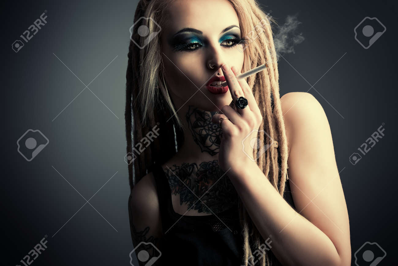 Sexy smoking girl with black make-up and long dreadlocks. Gothic style.  Fashion