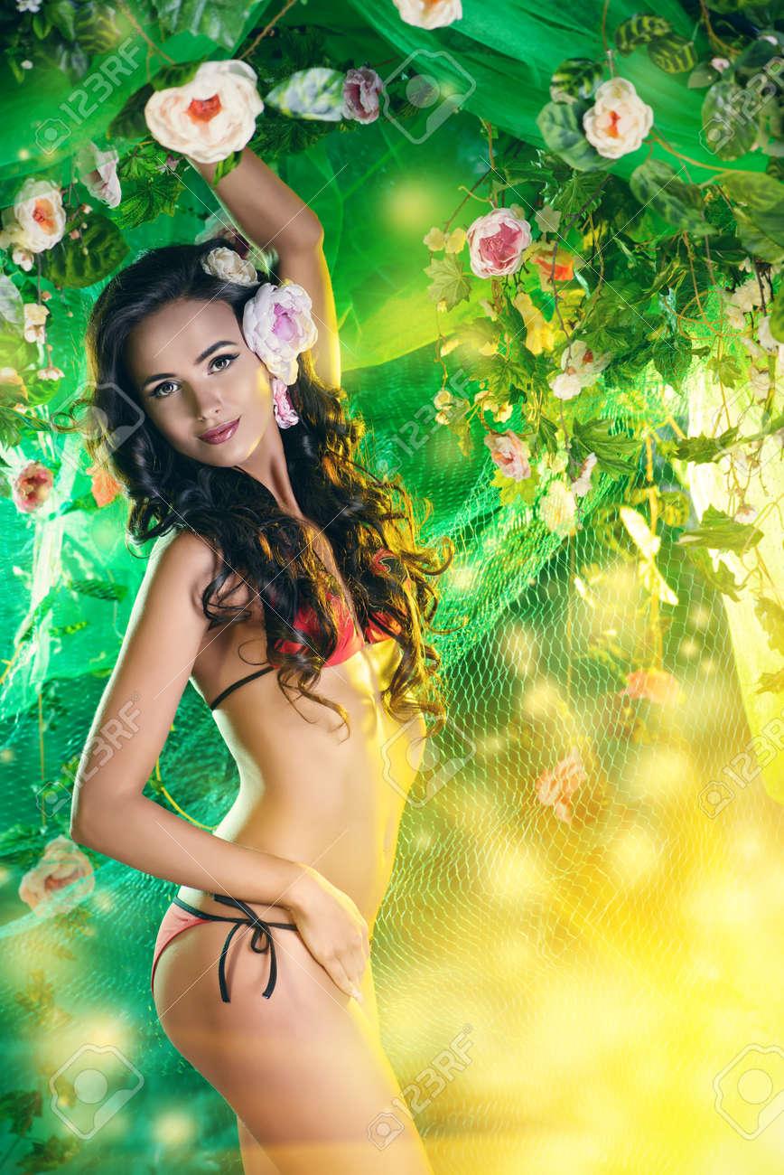 Beautiful brunette woman in bikini among tropical plants Stock Photo - 37048374