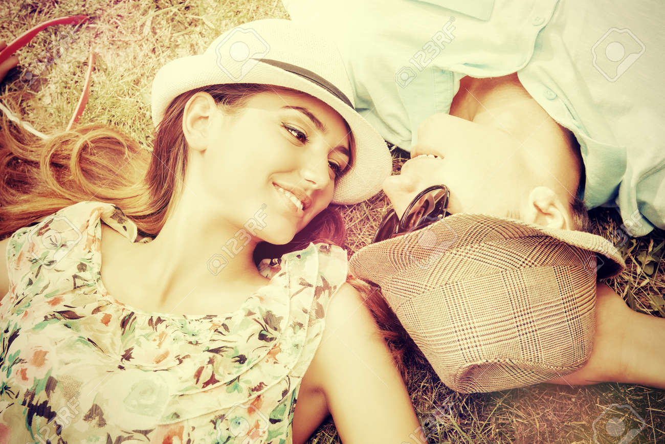 Happy young couple relaxing on the lawn in a summer park. Love concept. Vacation. - 37942362