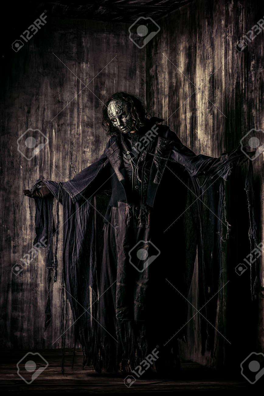 scary man in iron mask and black robe fantasy halloween stock photo